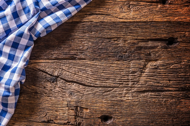 Toalha de mesa de cozinha quadriculada azul na mesa de madeira rústica.
