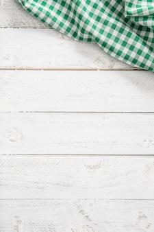Toalha de mesa de cozinha quadriculada verde na mesa de madeira.