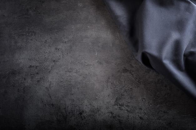 Toalha de mesa de guardanapo preta na placa de concreto preta.