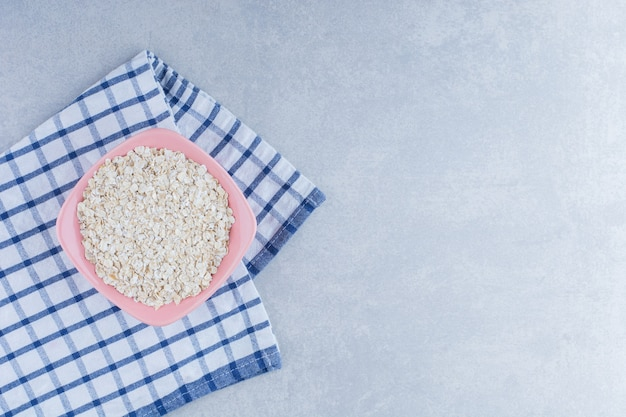 Toalha de mesa dobrada debaixo de uma tigela de flocos de aveia no fundo de mármore.