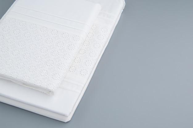Toalha de mesa nova dobrada com padrões bordados em um fundo cinza, vista de cima