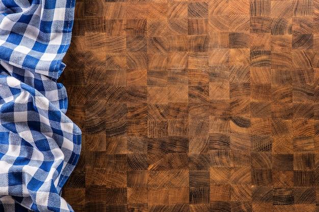 Toalha de mesa quadriculada azul do topo da vista na placa de madeira.