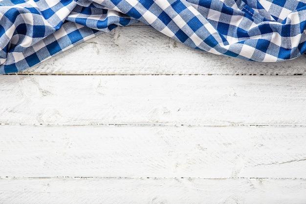 Toalha de mesa quadriculada azul na mesa de madeira.
