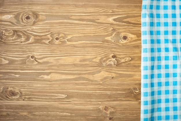 Toalha de mesa quadriculada azul na mesa de madeira