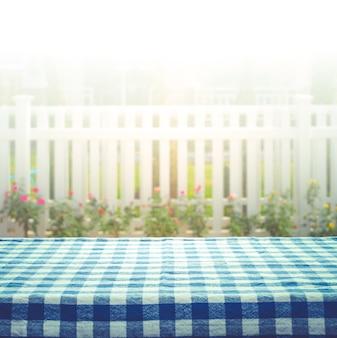 Toalha de mesa quadriculada em desfoque de cerca branca e fundo do jardim.