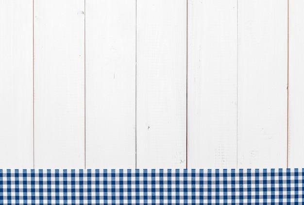 Toalha de mesa quadriculada na mesa de madeira