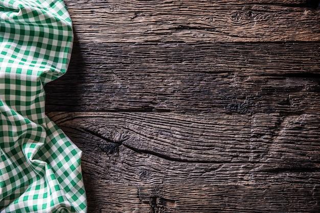 Toalha de mesa quadriculada verde na mesa de madeira rústica.