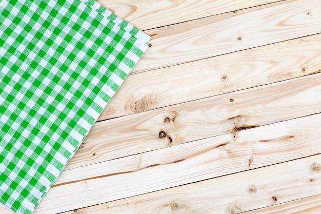 Toalha de mesa quadriculada verde na mesa de madeira