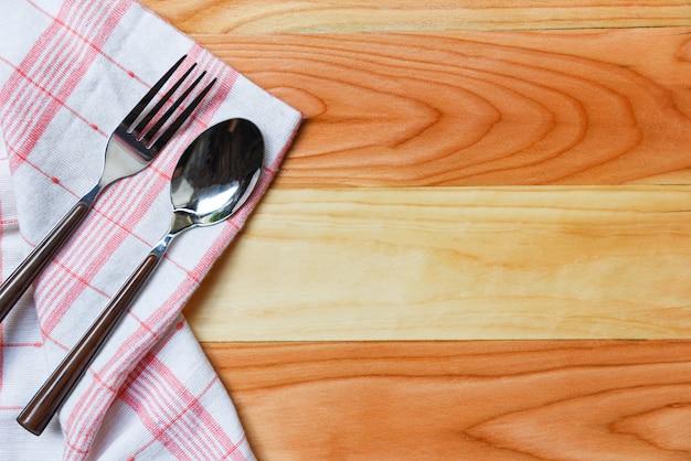Toalha de mesa quadriculada vermelha andwhite com garfo e colher na mesa de jantar de madeira - napery