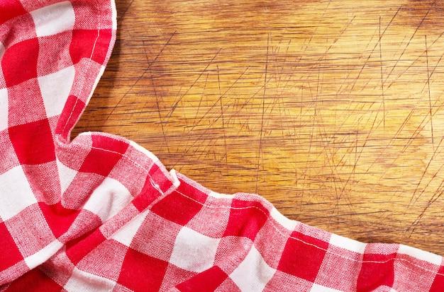 Toalha de mesa quadriculada vermelha em mesa de madeira, vista superior com espaço de cópia