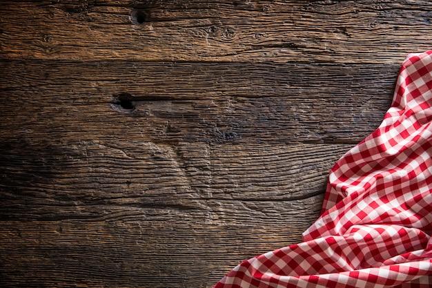 Toalha de mesa quadriculada vermelha na mesa de madeira rústica.