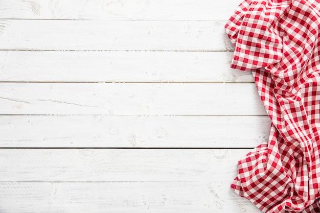 Toalha de mesa quadriculada vermelha na mesa de madeira.