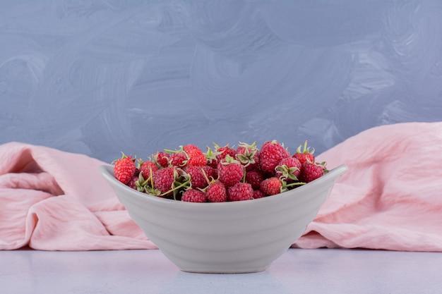 Toalha de mesa rosa atrás de uma tigela de framboesas em fundo de mármore. foto de alta qualidade