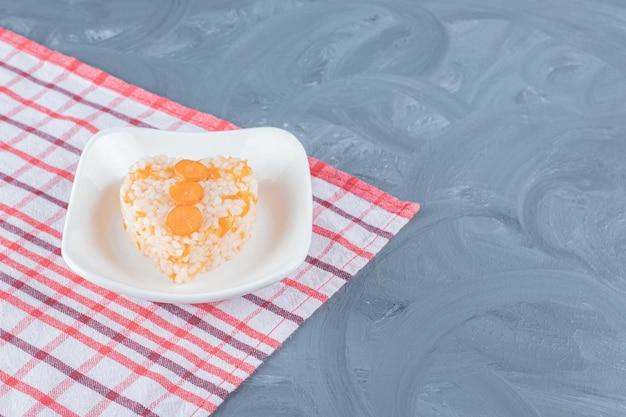 Toalha de mesa sob uma travessa de arroz cozido na mesa de mármore.