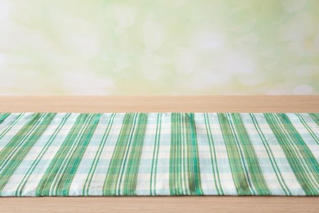 Toalha de mesa verde na mesa de madeira
