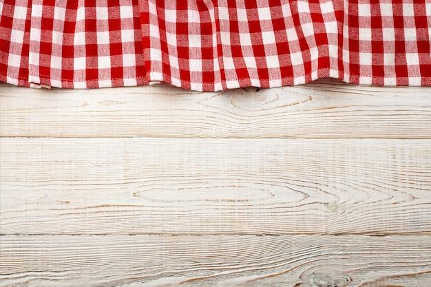 Toalha de mesa vermelha vazia na maquete de vista de cima da mesa de madeira.