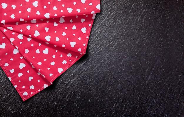 Toalha de mesa vermelha vazia, pedra e ardósia na maquete de vista superior de fundo preto.