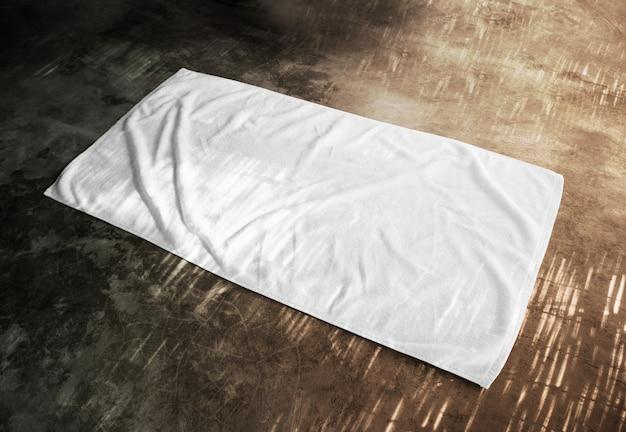 Toalha de praia branca em branco no chão texturizado