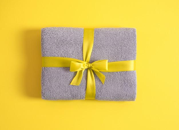 Toalha de terry cinza dobrada contra o fundo amarelo, toalha empilhada e amarrada pela fita amarela isolada