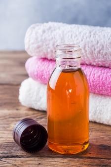 Toalha de terry e óleo cosmético para massagem.