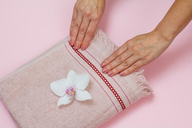 Toalha de terry macia com mãos femininas e flor de orquídea branca em fundo rosa. vista do topo.