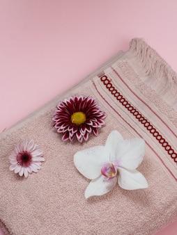 Toalha de terry macia com orquídea branca e botões de flores em fundo rosa. vista do topo.