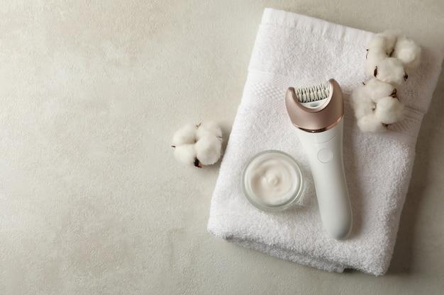 Toalha, depiladora, algodão e creme em branco