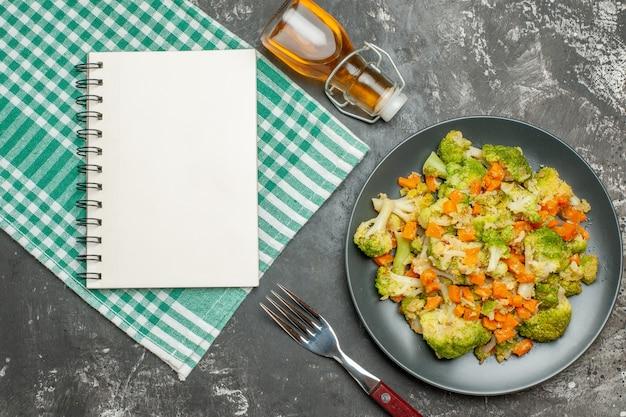 Toalha despojada de salada de vegetais fresca e saudável com garrafa de óleo caída e caderno