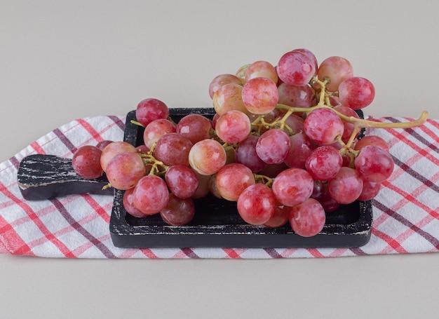 Toalha dobrada sob uma pequena bandeja com uvas vermelhas em mármore