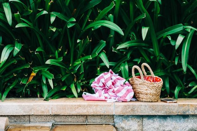 Toalha e cesta com acessórios de banho e banho de sol na borda de pedra à beira da piscina nos trópicos. ninguém