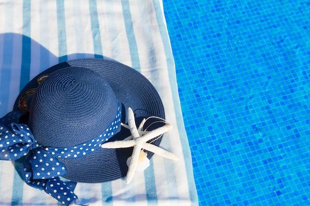 Toalha e chapéu azul de verão com estrela do mar perto da água da piscina