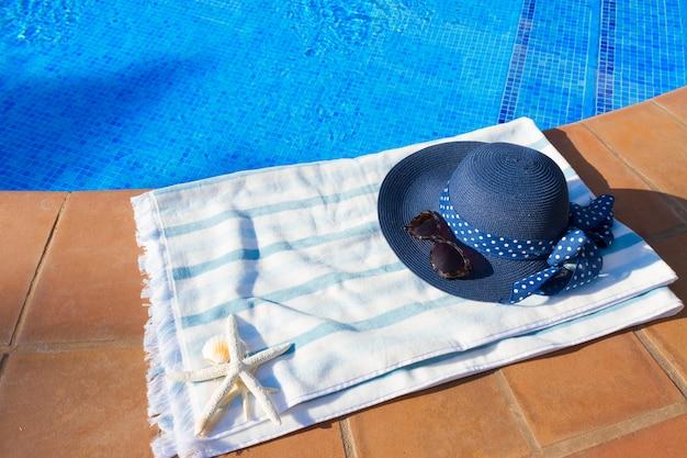 Toalha e chapéu azul de verão perto da piscina em dia ensolarado de verão