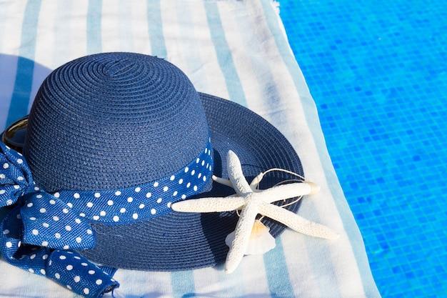 Toalha e chapéu de verão azul com conchas perto da água da piscina