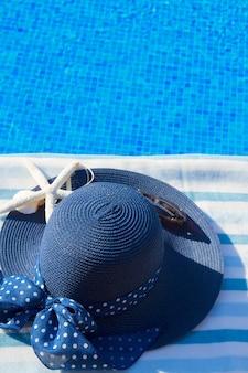 Toalha e chapéu de verão azul com conchas perto da piscina, copie o espaço na água azul
