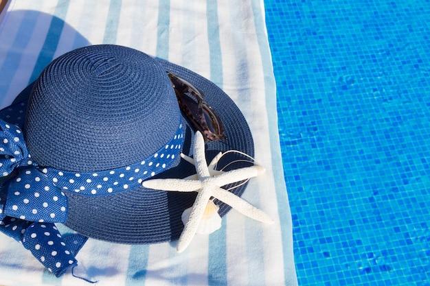 Toalha e chapéu de verão com conchas perto da água da piscina