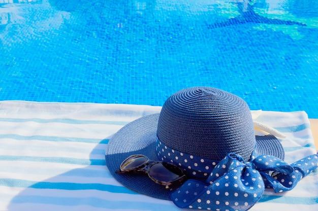 Toalha e chapéu de verão perto da água azul e clara da piscina