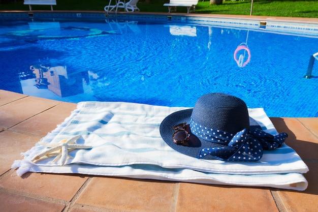 Toalha e chapéu de verão perto da piscina em dia ensolarado de verão