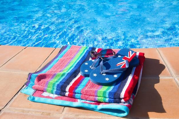 Toalha e sandália perto da água azul da piscina