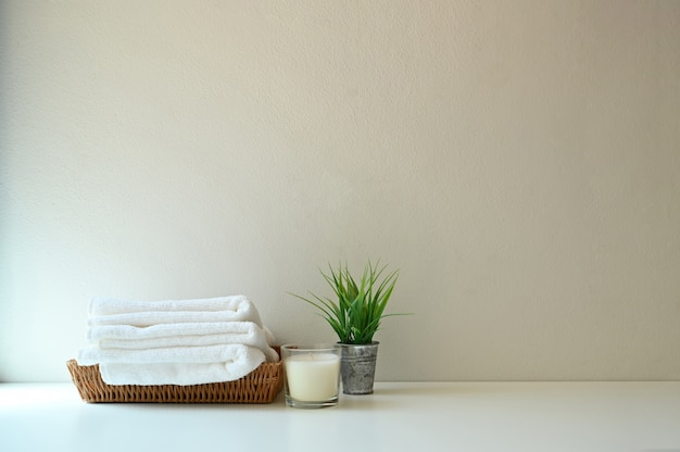 Toalha e vela dos termas na prateleira do banheiro com parede.