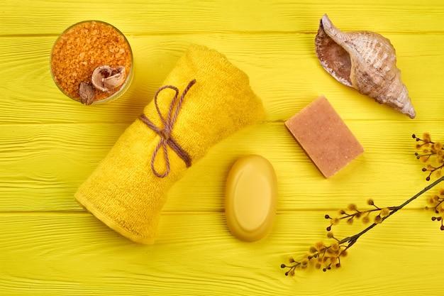 Toalha enrolada amarela com sabonete e vista superior da concha. ramo de salgueiro-bichano com camada plana de sal do himalaia.