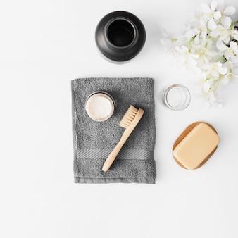 Toalha; escova; creme hidratante; sabonete; jarra e flores na superfície branca