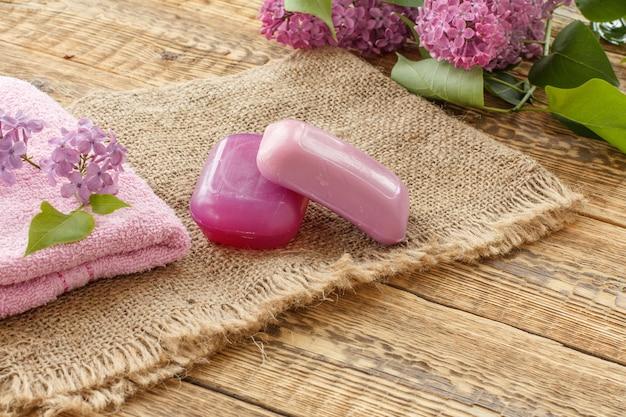 Toalha felpuda, sabonete para procedimentos de banheiro e flores lilás em pano de saco e tábuas de madeira velhas. produtos e acessórios de spa.