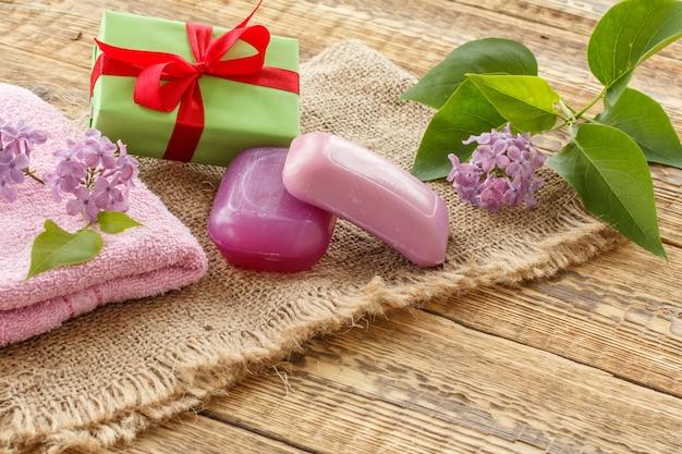 Toalha felpuda, sabonete para procedimentos de banho, caixa de presente e flores lilases em serapilheira e tábuas de madeira. produtos e acessórios de spa.