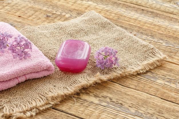 Toalha felpuda, sabonete para procedimentos de banho e flores lilases em serapilheira e tábuas de madeira. produtos e acessórios de spa.