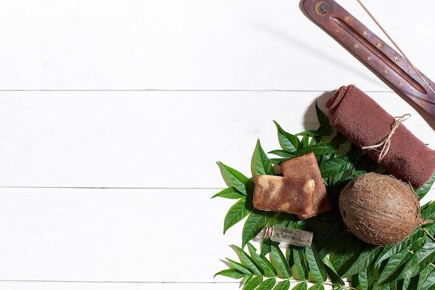 Toalha marrom, argila azul e sabonete de café natural na mesa de madeira branca, vista superior. ainda vida. fechar-se. postura plana. copie o espaço