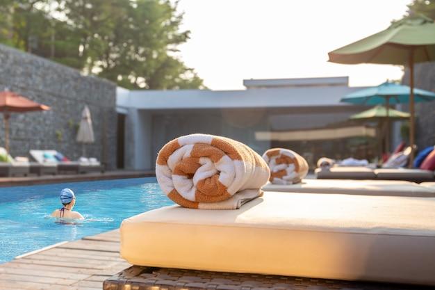 Toalha no sunbed com exercício do nadador da mulher na piscina.