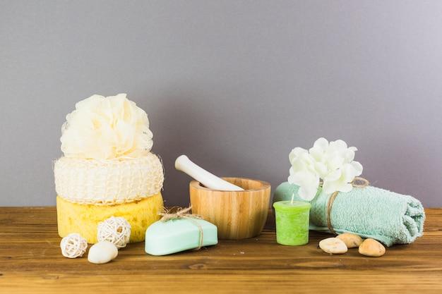 Toalha; pedras de spa; bucha; esponja; sabonete; vela; flor; almofariz e pilão na superfície de madeira