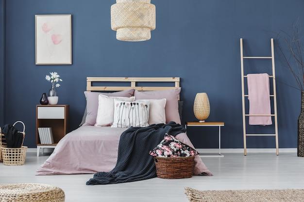 Toalha rosa na escada ao lado do armário de cabeceira com luminária de design no quarto com cama king-size