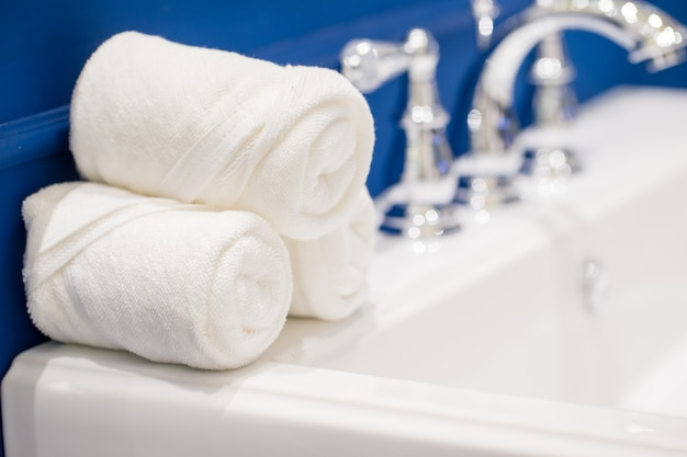 Toalhas brancas com sabonete líquido na mesa no banheiro