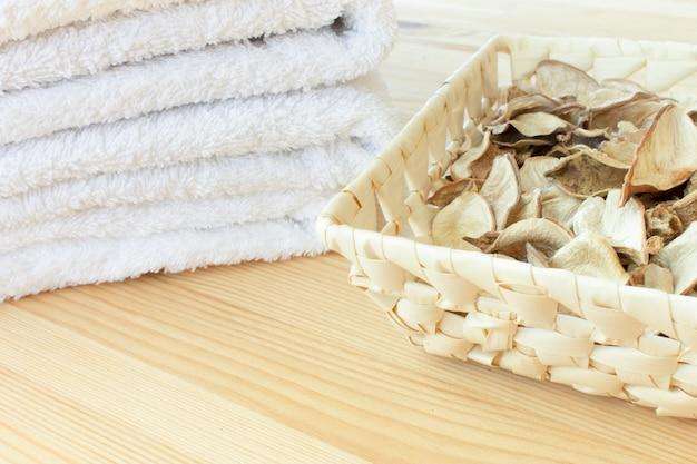 Toalhas brancas e cesto com plantas secas picantes, sobre um fundo claro de madeira